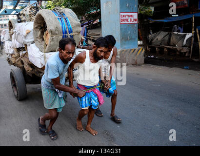 Workers pull a heavy cart of Cycle accessories in Kolkata, India - Stock Photo