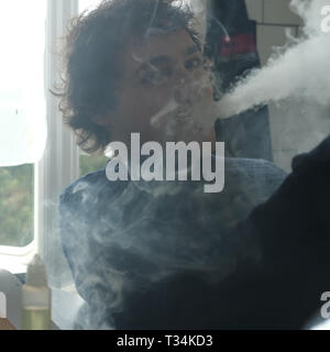 Man standing in kitchen vaping - Stock Photo