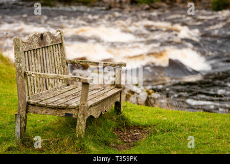 Wooden bench in front of river rapids on a walking train at Cassley Falls, Invercassley, Scotland. - Stock Photo