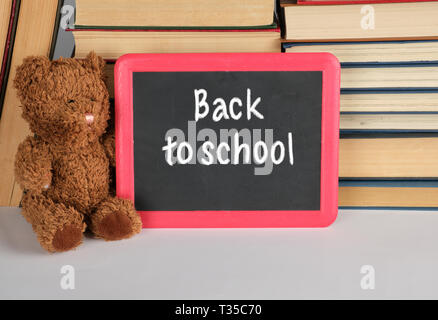 brown teddy bear and empty black board in red frame on the background of pile of books, concept back to school - Stock Photo