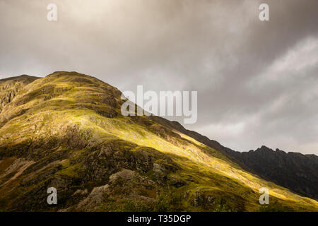 Sun filtering through clouds to selectively illuminate portions of the valley in Glencoe, Scotland. - Stock Photo