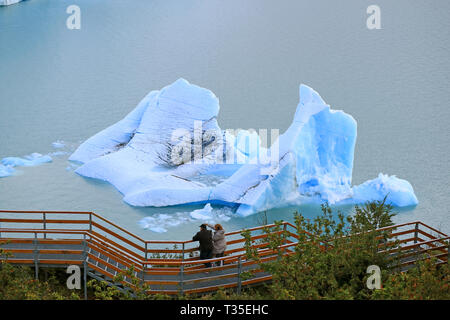 Two Visitors at the Viewing Balcony in front of the Huge Iceberg on Lake Agentino, Los Glaciares National Park, El Calafate, Argentina, South America - Stock Photo