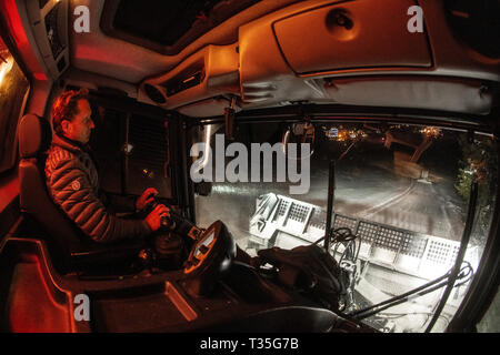 A view from the cab as a man drives a snowcat preparing ski pistes at night in the French alpine resort of Courchevel, Savoie. Piste basher. - Stock Photo