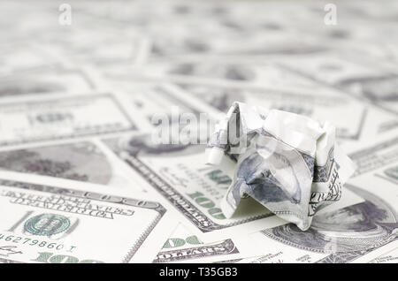 Crumpled dollar bill of the United States lies on the set of smooth money bills. Concept of unreasonable waste of money - Stock Photo