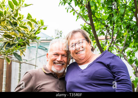 Portrait of cheerful happy senior aged couple smiling and having fun together in the garden looking at camera - retired lifestyle for nice caucasian p - Stock Photo