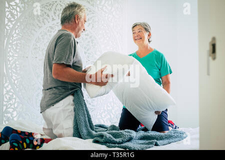 Pillows war at home for joke and to have fun together with senior mature caucasian couple playing in the bedroom - happiness and playful activity for  - Stock Photo