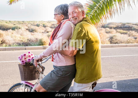 beautiful aged couple of senior in vacation go both on an old bike and enjoy the summer sunlight. tropical place and country side desert in background - Stock Photo