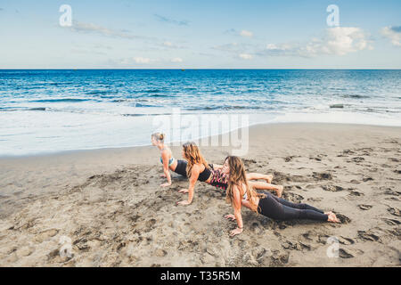 Pilates balance position three young active women at the beach doing sport fitness activity together under a dramatic cloudy sky - scenic image of peo - Stock Photo