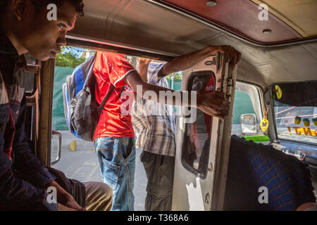 Dili, Timor-Leste - Aug 10, 2015: A teenage boy and other men inside a mikrolet bus driving with an open door, East Timor. Micro let minibus dangerous - Stock Photo