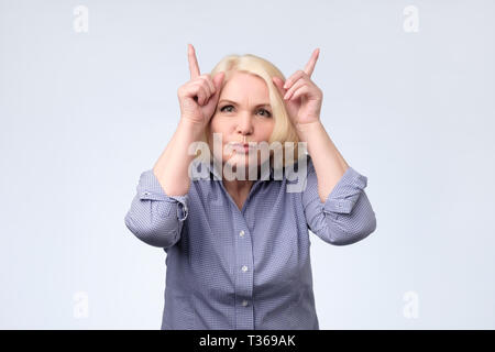 Funny joking senior blonde woman making horns with fingers. Studio shot - Stock Photo