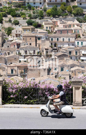 Man riding motorscooter in hill city of Modica Alta looking towards Modica Bassa, Sicily, Italy - Stock Photo
