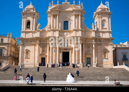 Bride arriving for wedding at Baroque style Cathedral of Saint Nicholas in Noto city, South East Sicily, Italy - Stock Photo