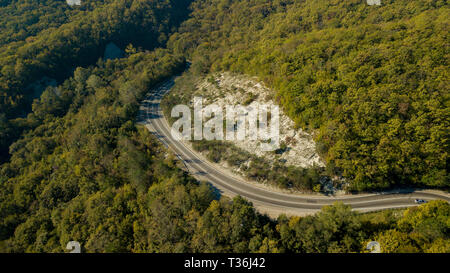 Aerial above view of a rural landscape with a curvy road running through it. Drone photography - Stock Photo