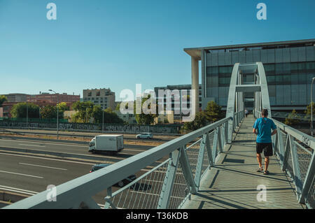 Man on walkway for pedestrians over highway with heavy traffic in Madrid. Capital of Spain with vibrant and intense cultural life. - Stock Photo