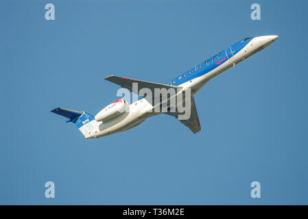 BMI British Midland International Embraer ERJ 145 jet airliner plane taking off from London Heathrow Airport London UK in blue sky with space for copy - Stock Photo