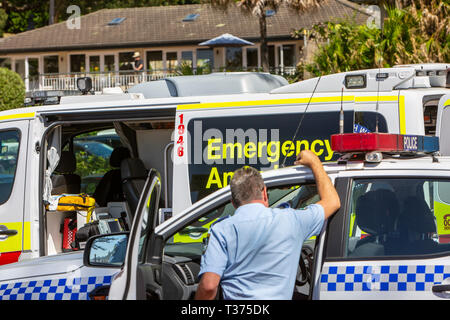 New South Wales police officer stood by police car and health ambulance at Palm beach,Sydney,Australia - Stock Photo