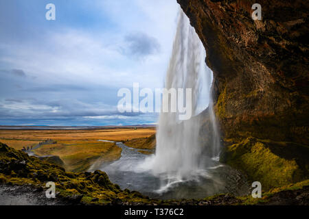 Seljalandsfoss is a waterfall that you can fully walk behind, situated on the South Coast of Iceland with a drop of 60 metres (200 feet). Due to the w - Stock Photo