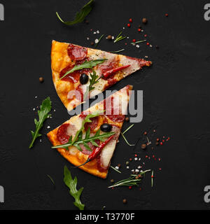 Pizza slices with rocket salad on black background - Stock Photo