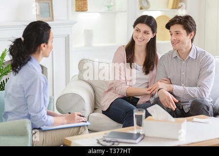 Counselor and happy couple after effective marital therapy - Stock Photo