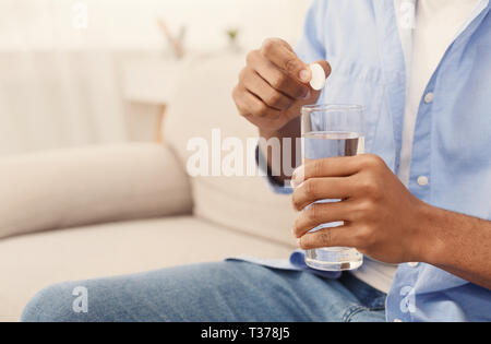 Sick black guy dropping aspirin pill into glass of water, sitting on couch at home, free space - Stock Photo