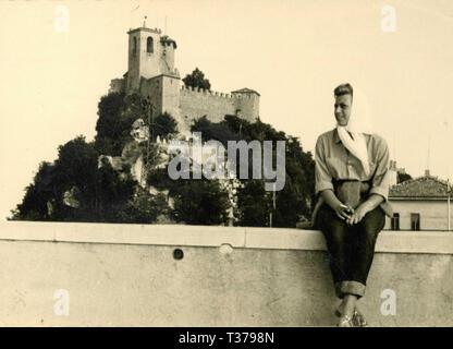 Woman with headscarf sitting on the wall, San Marino Republic 1960s - Stock Photo