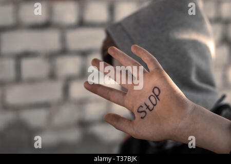 the boy closes his hand, written on his hand stop, cruelty to children - Stock Photo