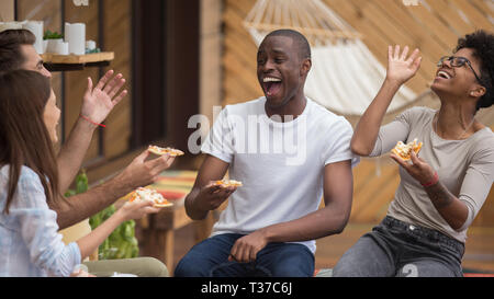Happy diverse friends talking laughing sharing dinner in cafe - Stock Photo