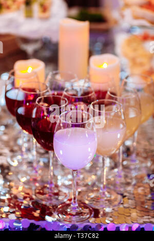 Beautiful row line of different colored alcohol cocktails on a party, martini, vodka, tequila and others on decorated catering bouquet table on open a - Stock Photo