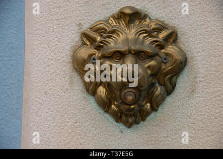 Door bell with a lion's head, antiqued burnished brass button. Electrified doorbell button of a house in Burano, Venice. - Stock Photo