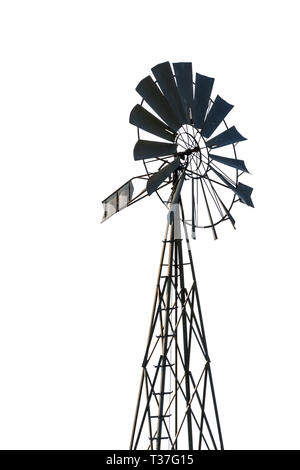 Low angle view of an old-fashioned, multi-bladed, metal wind pump atop a lattice tower in backlight, cut out on white background. - Stock Photo