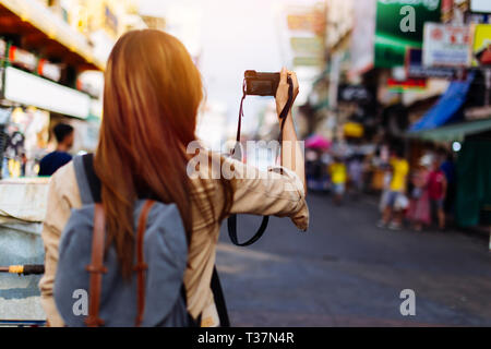 Young female tourist woman holding a camera and taking photos in Bangkok, Thailand while travelling in Southeast Asia Stock Photo