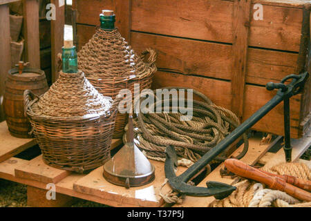 Composition with old wooden cart and wine flasks with old rope and anchor in Italy - Stock Photo