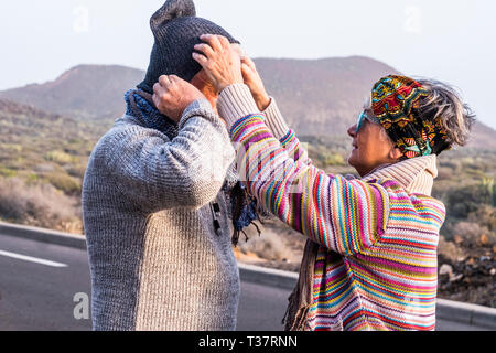 Aged coloured happy fashion hippy couple senior people in outdoor leisure activity together in couple - cold season and woman help husband with the wa - Stock Photo