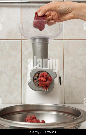 hand of woman making forcemeat with electrical meat grinder in the kitchen - Stock Photo