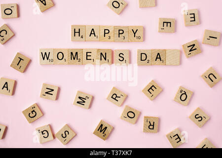 Top view Message happy woomans day spelled in wooden blocks on pink background. Love, 8 march background. Gift, greeting, compliment concept. Copy spa - Stock Photo
