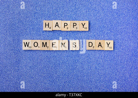 Top view Message happy woomans day spelled in wooden blocks on blue background. Love, 8 march background. Gift, greeting, compliment concept. Copy spa - Stock Photo