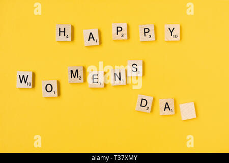 Top view Message happy woomans day spelled in wooden blocks on yellow background. Love, 8 march background. Gift, greeting, compliment concept. Copy s - Stock Photo