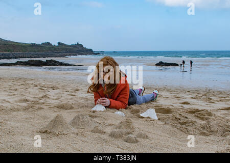 St Ives, Cornwall, UK. 7th April 2019.  The public were invited to cover the beach at St Ives with tiny mountains, made from moulds to represent Mount Kilmanjaro,  Shasta, Fuji, Stromboli and Ulura. Seen here Agatha Fitch.  The event today organised by the Tate St Ives is one of several taking place around the UK in conjunction with artist Katie Paterson. Credit: Simon Maycock/Alamy Live News - Stock Photo