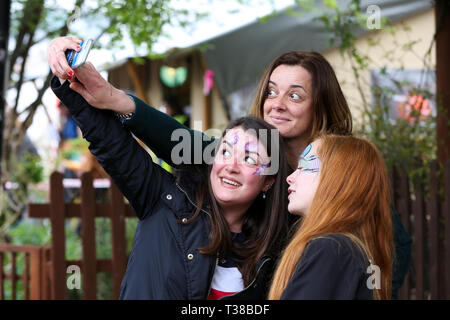 London, UK, UK. 7th Apr, 2019. Spectators are seen taking a selfie before the Oxford vs Cambridge Goat Race in East London.Two pygmy goats compete during the 10th Oxford and Cambridge Goat Race at Spitalfields City Farm, Bethnal Green in East London. The annual fundraising event, which takes place at the same time as the Oxford and Cambridge boat race, where two goats, one named Hamish representing Oxford and the other Hugo representing Cambridge to be crowned King Billy. Credit: Dinendra Haria/SOPA Images/ZUMA Wire/Alamy Live News - Stock Photo