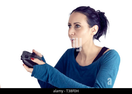 Young woman with blue sweater playing video game on wireless gaming controller with a concentrated facial expressions isolated on white - Stock Photo