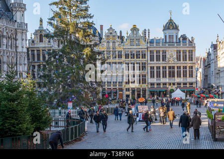 Tourists on the famous Grand Place in Brussels, with rich sculptural decorated guild houses facades and Christmas trees. - Stock Photo