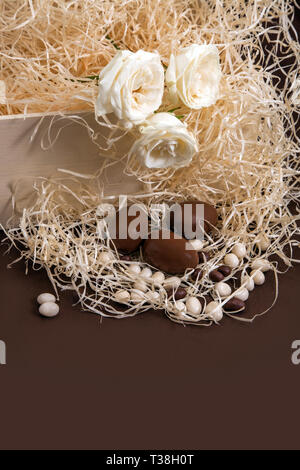 Chocolate bunny and three eggs in box with straw. Easter traditional celebtation in Netherlands with gifts and roses on yellow straw background. - Stock Photo