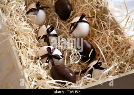 Chocolate brown and white eggs with ribbons in box with straw. Easter traditional celebtation in Europe with gifts on yellow straw background. - Stock Photo