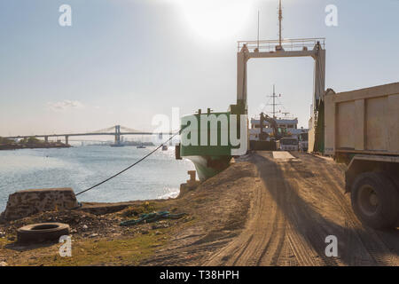 unload soil from a transportship with a ship crane on heavy trucks driving on off a ramp up and down the frighter - Stock Photo