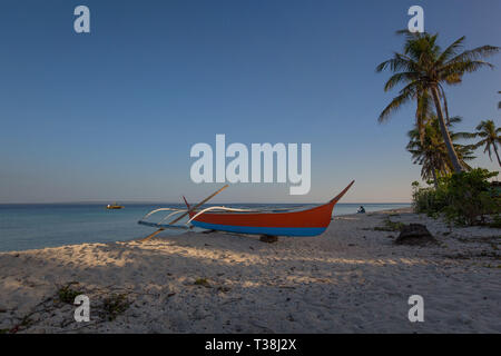 outrigger dive boat at the beach on the white sand, in a tranquil summer sunny day background photo - Stock Photo