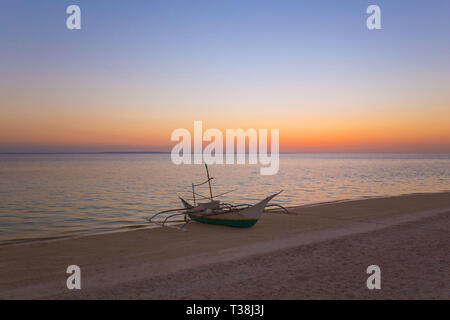 outrigger fisher boat at the beach on the white sand, in a tranquil summer sunset dusk background photo - Stock Photo