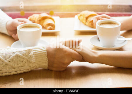 Close up of young couple holding hands together while having romantic lunch in cozy french cafe. Man and woman keeping their hands together and drinki - Stock Photo