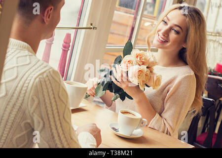 Portrait of young couple having romantic dinner at cozy french cafe. Beautiful woman holding flower bouquet in hands and smiling while sitting in rest - Stock Photo