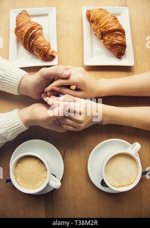 Top view man and woman holding their hands together while having lunch in cozy french cafe. Young romantic couple holding hands together. Cups of coff - Stock Photo