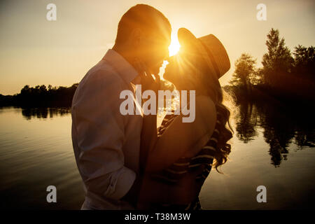 Happy loving couple. Silhouette of young man hugging and kissing his beautiful girlfriend while standing face to face to each other on the beach with  - Stock Photo